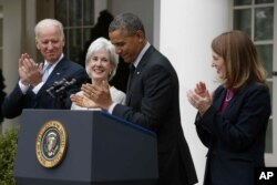 President Barack Obama and Vice President Joe Biden stand with outgoing Health and Human Services Secretary Kathleen Sebelius, second from left, and his nominee to be her replacement, Budget Director Sylvia Mathews Burwell, April 11, 2014.