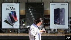 FILE - A woman checks her phone as she walks by posters adverting smartphones at a mobile phone store in Seoul, South Korea, Oct. 17, 2017.