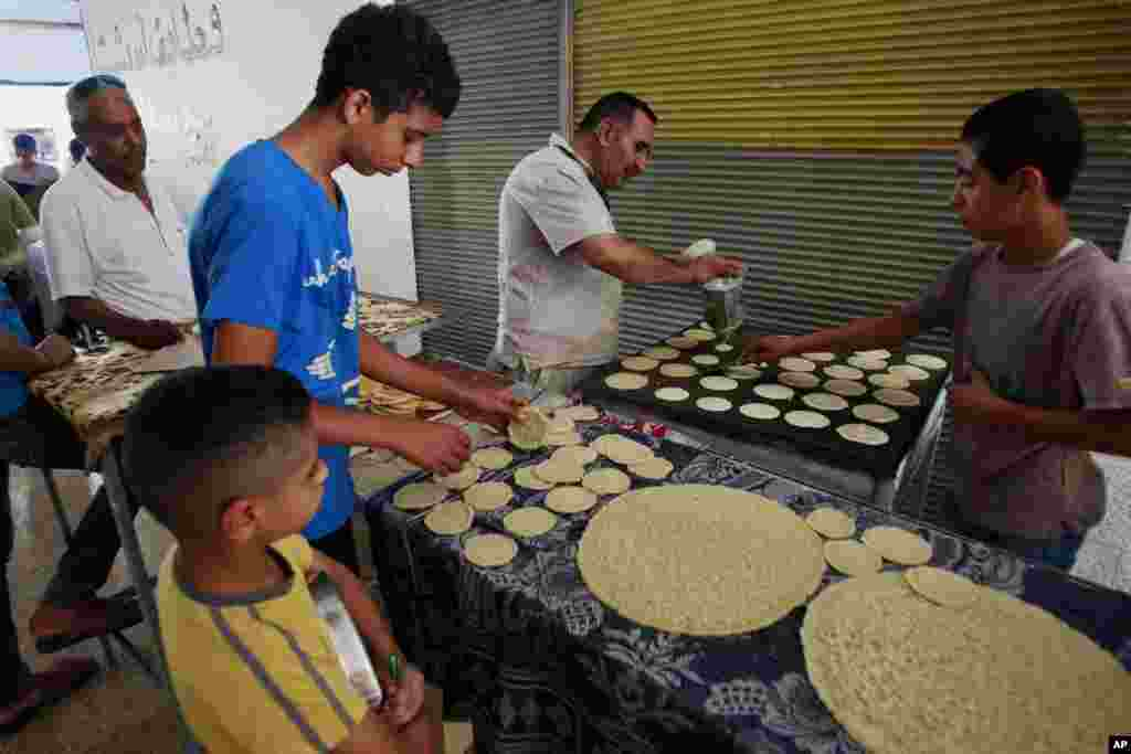 Palestinian vendors make pancakes for sale. The pancakes are usually filled with cheese or nuts and made at home, in the West Bank city of Jenin, June 29, 2014.