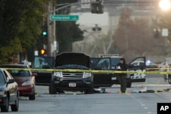An investigator looks at a black SUV that was involved in a police shootout with suspects, Dec. 3, 2015, in San Bernardino, California.