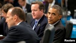 Presiden AS Barack Obama duduk bersama Perdana Menteri Australia (kiri) dan PM Inggris David Cameron dalam sidang paripurna KTT pemimpin G20 di Brisbane November 15, 2014. Western leaders attending a G20 summit bl