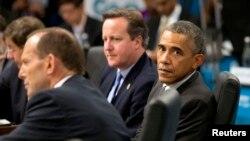 Presiden AS Barack Obama (kanan) duduk di samping Perdana Menteri Australia Tony Abbott (kiri) dan Perdana Menteri Inggris David Cameron dalam sebuah sidang di KTT pemimpin G20 di Brisbane, 15 November 2014.