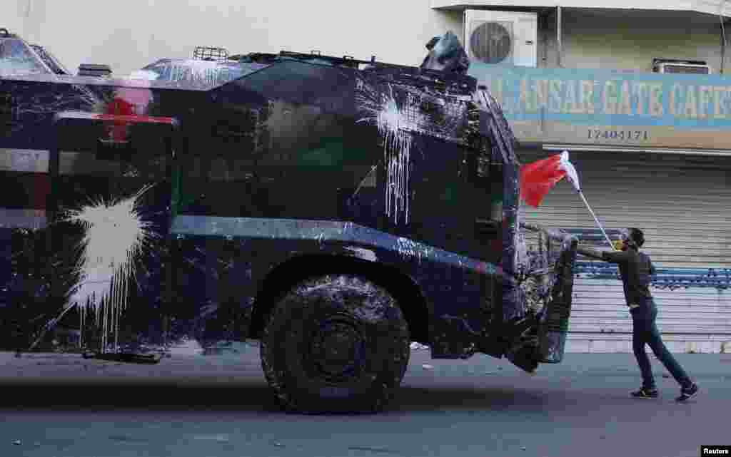 A protester, holding a Bahraini flag, confronts a riot police armored personnel carrier in an attempt to stop it from entering the village of Bilad Al Qadeem, south of Manama. Bahraini police fired rubber bullets and tear gas to scatter protesters who gathered outside the home of Sheikh Ali Salman, a Shi'ite Muslim opposition leader, witnesses said, after he was remanded in custody for a further 15 days.