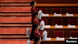 Các nữ tiếp viên chờ đợi để rót trà cho các đại biểu tham dự phiên họp Đại hội Đại biểu Nhân dân Toàn quốc tại Đại sảnh đường Nhân dân ở Bắc Kinh, ngày 5/3/2015.