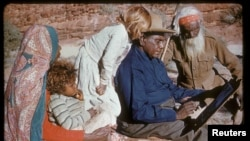 FILE - An undated photo released Oct. 14, 2017, shows family members watching Australia's most famous Aboriginal artist, Albert Namatjira, sitting on a rock as he paints.
