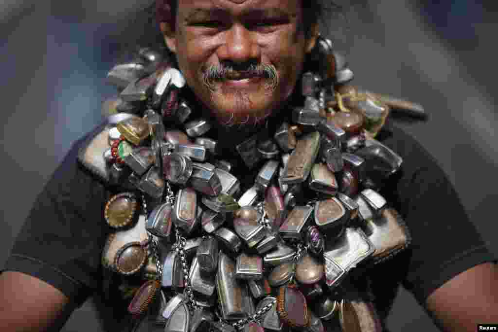 A protester wears a chain with many amulets as he joins others in a march towards central Bangkok, Thailand. Thousands of people took to the streets of the Thai capital after lawmakers approved a draft political amnesty bill that could allow the return of self-exiled former premier Thaksin Shinawatra.