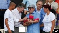 El presidente de Colombia, Juan Manuel Santos (segundo desde la izquierda) y el principal comandante de las FARC, Rodrigo Londoño, alias Timoleón Jiménez o Timochenko (tercero desde la derecha) saludan al bebé de ua pareja rebelde en un acto para conmemorar el fin del desarme, en Buenavista, Colombia, el martes, 27 de junio de 2017.