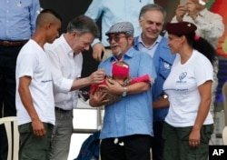 FILE - Colombia's President Juan Manuel Santos, second left, and the Revolutionary Armed Forces of Colombia, FARC, top commander Rodrigo Londono also known as Timoleon Jimenez or Timochenko, third left, greet the baby of a rebel couple during an act to commemorate the completion of the FARC disarmament process in Buenavista, Colombia, June, 27, 2017.