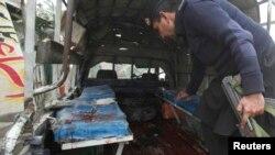 一辆警察的箱型车在白沙瓦郊外的恰尔萨区遭遇炸弹袭击。图为事发后警察在被炸毁的车内搜集证据。(2014年1月22日)