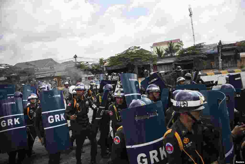 Police use batons and shields during clashes with garment workers in Phnom Penh, Cambodia, Nov. 12, 2013.