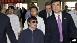 In this file photo taken May 2, 2012 and released by the US Embassy Beijing Press Office, blind activist Chen Guangcheng, center, holds hands with US Ambassador to China, Gary Locke, at a hospital in Beijing.