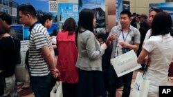 "Visitors chat as others seek information about the U.S. government's EB-5 visa program at the ""Invest in America Summit,"" a day after an event promoting EB-5 investment in a Kushner Companies development was held, at a hotel in Beijing, May 7, 2017."