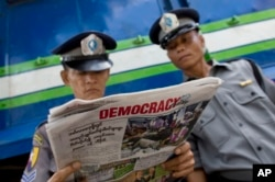 "Police officers read a copy of the newspaper ""Democracy Today"" in Yangon, Myanmar, Wednesday, Nov. 11, 2015."