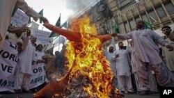 巴基斯坦示威人群於去年11月27日在首都卡拉奇焚燒象徵美國的肖像﹐抗議北約越境空襲造成嚴重死傷。(資料圖片)