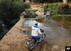 Syrian men cross the Kabir River into Syria from Wadi Khaled, Lebanon, October 13, 2011.