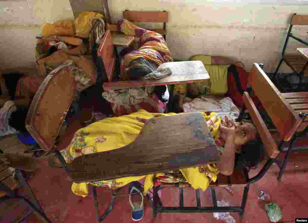 A small girl rests on a school desk inside an evacuation center after Typhoon Rammasun battered the coastal bay of Baseco compound, metro Manila, July 16, 2014.