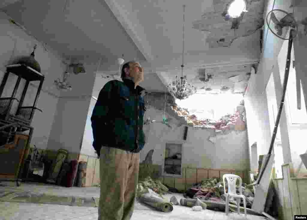 16일 시리아 홈스 시의 무너진 모스크를 점검하는 남성.