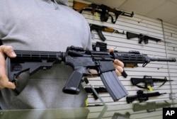 伊利诺伊州的一位枪支店主展示他出售的AR-15步枪。(资料照)