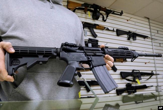 伊利諾伊州的一位槍支店主展示他出售的AR-15步槍。 (資料照)