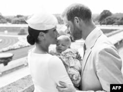 Pangeran Harry yang bergelar Duke of Sussex (kanan) dan istrinya, Meghan, Duchess of Sussex memeluk bayi laki-laki mereka, Archie Harrison Mountbatten-Windsor di Kastil Windsor dalam foto resmi upacara pembaptisan Archie, Sabtu, 6 Juli 2019. (Foto: Chris