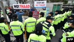Police surround anti-war activists holding banners demonstrating against the Terminal High Altitude Area Defense (THAAD) anti-ballistic missile system outside the Foreign Ministry in Seoul, March 17, 2015.