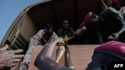 FILE - Rebel troops of the Sudan People's Liberation Army in Opposition (SPLA-IO) unload their weapons at their military site in Juba, April 25, 2016.