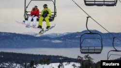 Snowboarders ride a lift with Lake Tahoe in the background at Squaw Valley in Olympic Valley, California, Dec. 5, 2015.