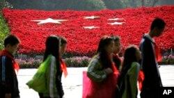 Siswa di Shanghai, China berjalan di depan hamparan bunga (foto: dok).