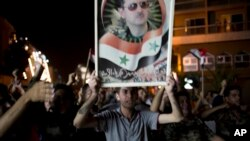FILE - Syrian soldiers celebrate Bashar al-Assad's presidential re-election, in Damascus, Syria, June 4, 2014.