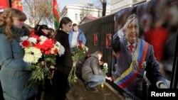 Люди несут цветы к посольству Венесуэлы. Минск, Беларусь. 6 марта 2013 года