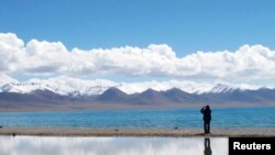 FILE - A tourist takes pictures in the Tibet Autonomous Region, Sept. 14, 2011.