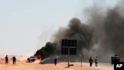 반군의 공격을 받은 카다피 친위부대 픽업트럭에서 화염이 치솟고있다.