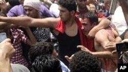 一名埃及示威者5月2日在开罗的抗议人群中保护一名身份不明的袭击者免遭其他示威者的殴打