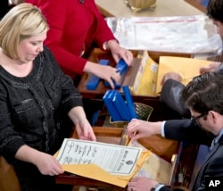 FILE - Clerks unseal the certificates of results from all fifty states during a meeting of the U.S. Electoral College in the House of Representatives on Capitol Hill in Washington, Jan. 4, 2013. Never since its creation in 1787 has the Electoral College not endorsed the candidate who won most of its 538 votes.