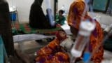 A woman displaced from a drought-stricken area takes care of her baby boy, who is suffering stomach infection, at the Civil Hospital in Mithi, in the Sindh province March 12, 2014. Dozens of children have died of malnutrition and other causes in Pakistan'