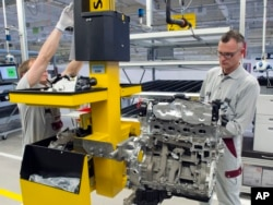 FILE - Workers complete a new diesel engine at the MDC Power GmbH, a company of the German Daimler AG, in Koelleda, Germany, Oct. 23, 2015.