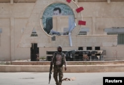 FILE - A Kurdish fighter from the People's Protection Units (YPG) carries his weapon as he walks at the faculty of economics where a defaced picture of Syrian President Bashar al-Assad is seen in the background, in the Ghwairan neighborhood of Hasaka, Syria, Aug. 22, 2016.