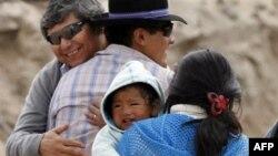 Juan Aguilar, trái, và Carlos Mamani là hai thợ mỏ đầu tiên đến dự thánh lễ theo nghi thức Công giáo hôm Chủ nhật, 17/10/2010