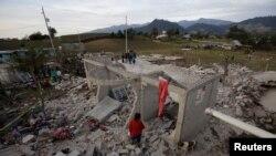 Warga berdiri di samping puing-puing bangunan setelah kembang api yang disimpan di sebuah rumah meledak di San Isidro, Chilchotla, Meksiko, 9 Mei 2017.