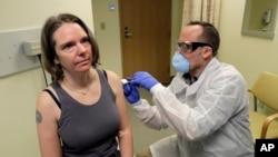 Seorang petugas medis memberikan suntikan pertama vaksin kepada Jennifer Haller (kiri), dalam uji klinis tahap pertama vaksin virus corona COVID-19, di Kaiser Permanente Washington Health Research Institute in Seattle, 16 Maret 2020. (Foto: AP)