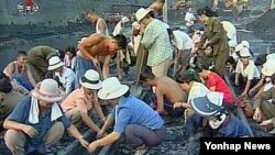 폭우 피해로 인해 철길복구 작업을 하고 있는 북한 평안남도 개천시의 주민들. (조선중앙TV 화면 캡처)
