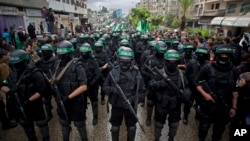 Masked Palestinian Hamas gunmen perform their military skills during a rally.