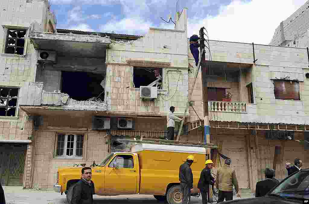 This handout photo shows workers at buildings SANA says were destroyed by opposition forces in Baba Amr, Homs, March 14, 2012. (Reuters/SANA)