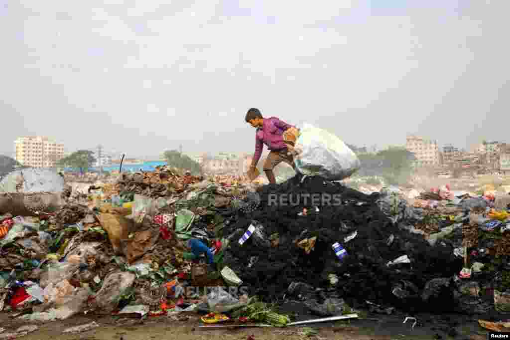 A boy collects materials from waste dumped in the bank of Buriganga River in Dhaka, Bangladesh.