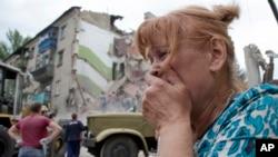 Phụ nữ Ukraine bật khóc gần căn nhà bị đổ sập sau vụ không kích ở thị trấn Sniznhe, miền đông Ukraine, ngày 15/7/2014.