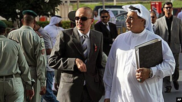 Bahraini lawyer Mohamed al-Tajer, right in white, walks away from the Manama, Bahrain, courthouse where the first session of a heavily guarded trial opened for more than two dozen Shiite activists accused of plotting against Bahrain's Sunni rulers. The de