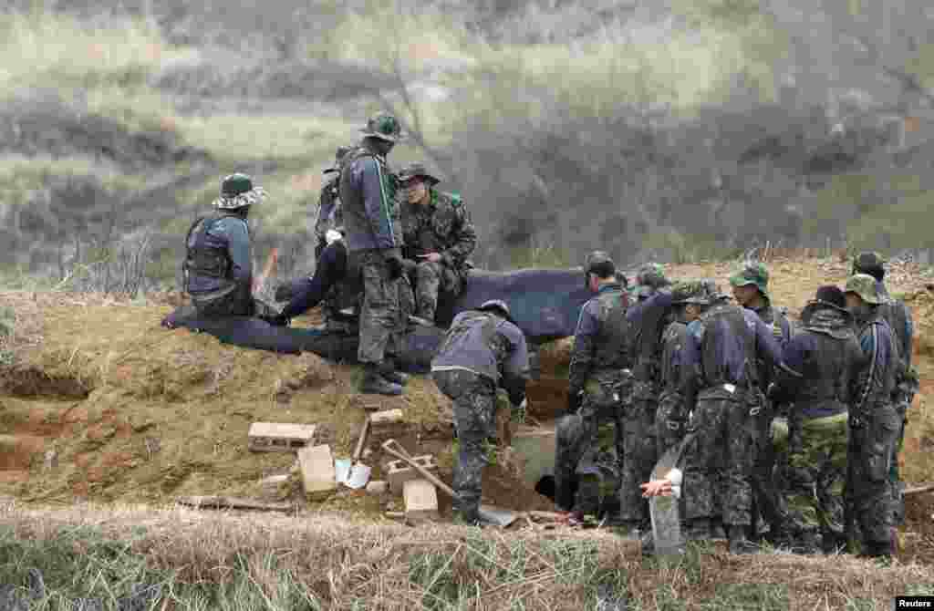 South Korean soldiers talk as they repair a trench near the demilitarized zone separating North Korea from South Korea in Paju, north of Seoul, April 15, 2013.