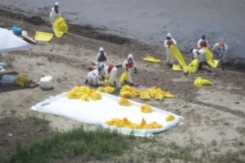 Workers clean up oil along a beach at South Pass, La. May 11, 2010 near where the Mississippi River meets the Gulf of Mexico.