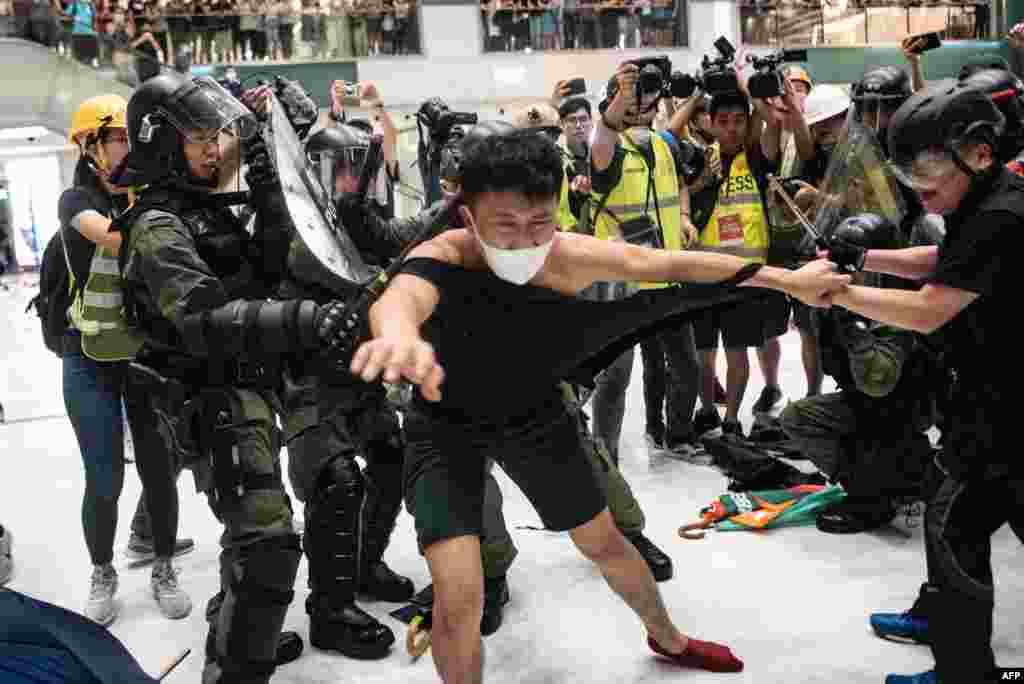 Polisi menarik baju kaus seorang demonstran saat bentrokan di dalam pusat perbelanjaan di distrik Sha Tin, Hong Kong dalam aksi protes menentang RUU Ekstradisi yang kontroversial.