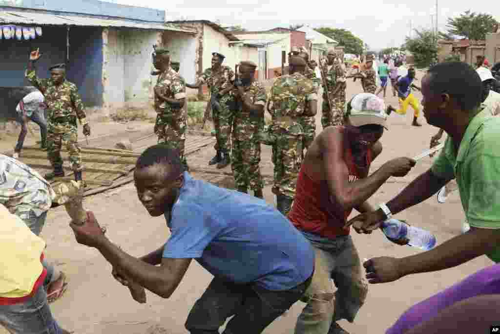 Des soldats tirent en l'air pour disperser des manifestants qui ont acculé Jean Claude Niyonzima un membre présumé de la milice Imbonerakure de la jeunesse du parti au pouvoir dans un égout dans le quartier de Cibitoke de Bujumbura, au Burundi, jeudi 7 mai 2015.